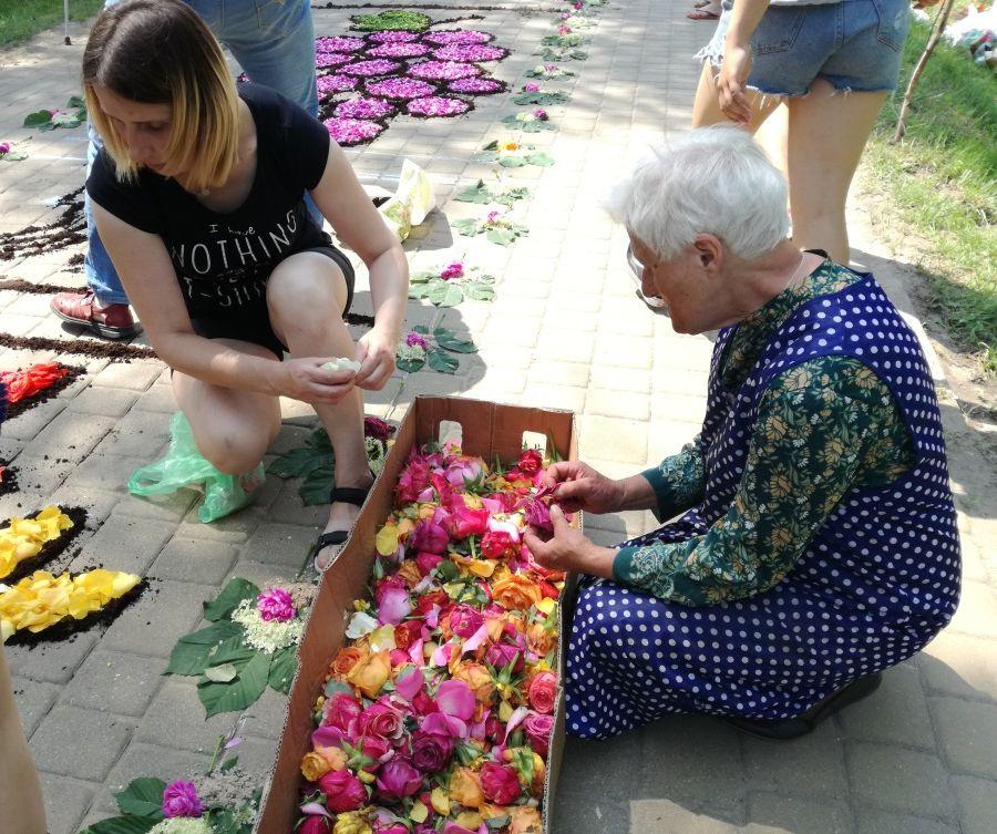 Podział pracy podczas układania dywanów: młodzi sypią, a starsi skubią i przebierają kwiaty. Spycimierz, Boże Ciało, fot. K. Smyk